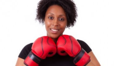 Overweight young black woman holding boxing gloves - African people