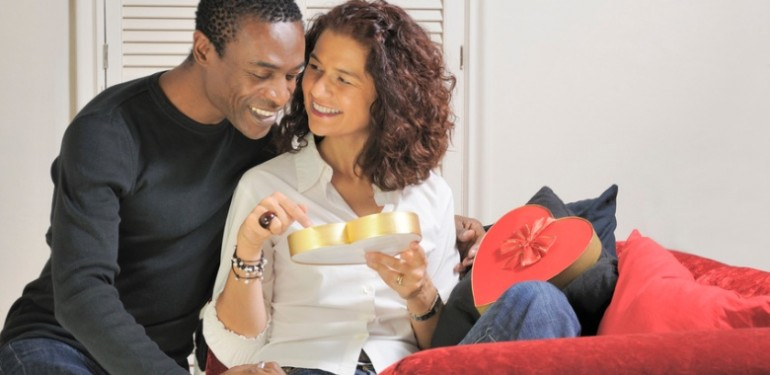Man and woman relax together with a heart shaped chocolate box