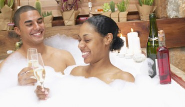 Couple in bubble bath drinking champagne